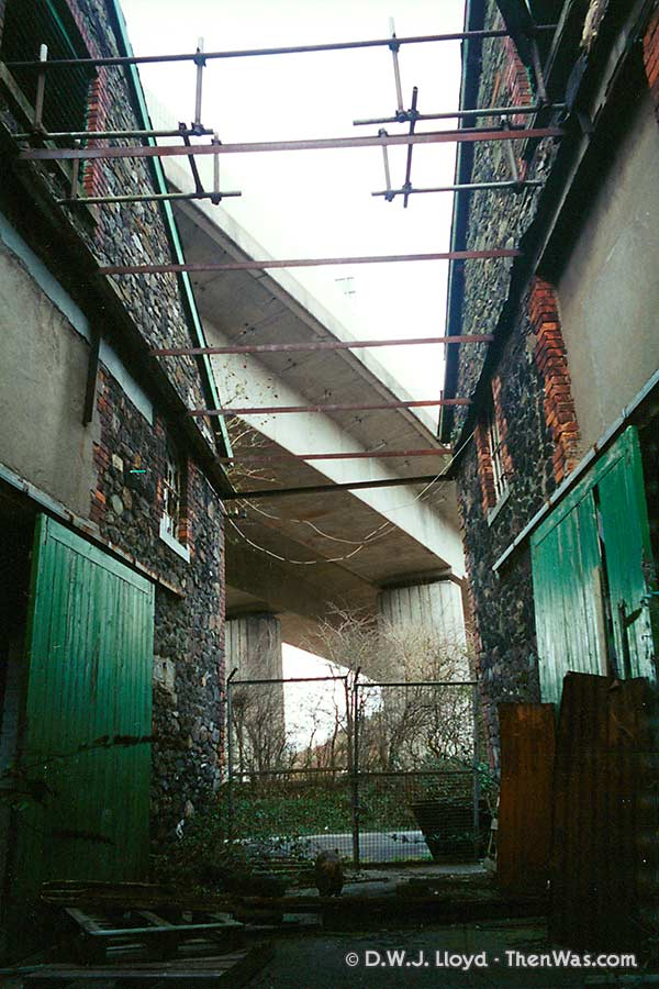 View between the derelict buildings under the flyover